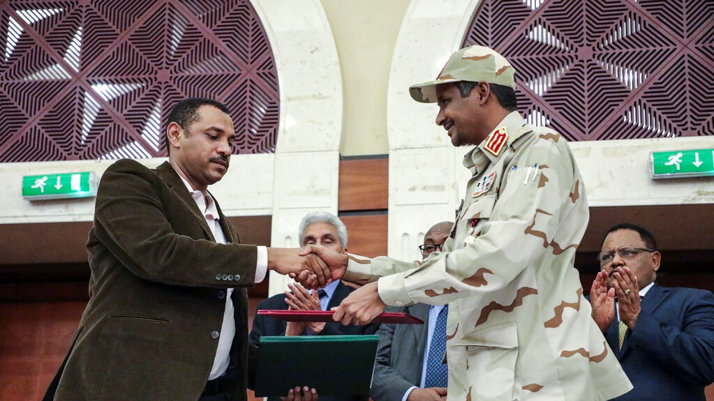 Gen. Mohammed Hamdan Dagalo, right, and Sudan's pro-democracy movement leader Ahmad al-Rabiah shake hands after signing a power sharing document in Khartoum, Sudan, Wednesday, July 17, 2019. (AP Photo/Mahmoud Hjaj)