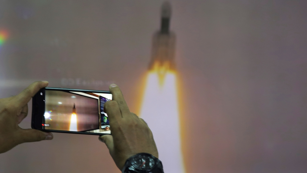 A man at New Delhi's Nehru Planetarium, takes pictures of a web cast of the lift off of Indian Space Research Organization (ISRO)'s Geosynchronous Satellite launch Vehicle (GSLV) MkIII carrying Chandrayaan-2 from Satish Dhawan Space center in Sriharikota, India, Monday, July 22, 2019. India's space agency says it has launched an unmanned spacecraft to the far side of the moon a week after aborting the mission due to a technical problem. (AP Photo/Manish Swarup)