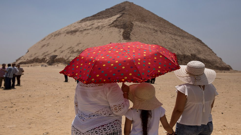 Women visit the Bent Pyramid during an during an event opening the pyramid and its satellites for visitors in Dashur, Egypt, Saturday, July 13, 2019. The Bent pyramid, listed on UNESCO's world heritage list as part of the Memphis necropolis, is considered a transition phase in pyramids construction that comes between step pyramids and complete pyramids. (AP Photo/Maya Alleruzzo)