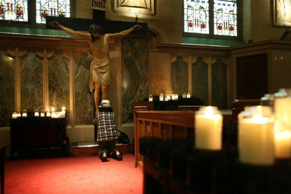 Image d'illustration d'une femme priant dans une église de San Francisco afp.com - JUSTIN SULLIVAN