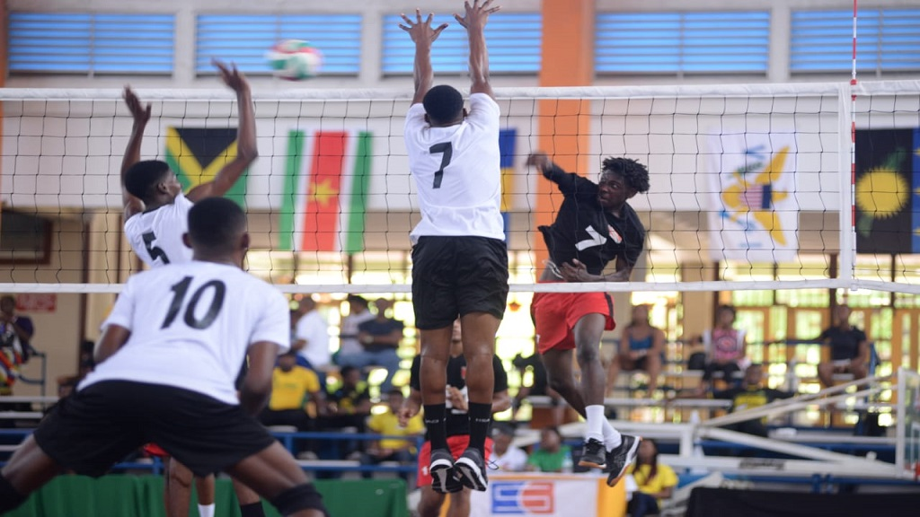 Jamaica's Damion Smith (right) and Clive Walter (left) block a spike  from Trinidad and Tobago's Julius Ghouralal during the boys' 19 and under third-place playoff match at the  CAZOVA championships on Saturday, July 27, 2019 at G C Foster College.