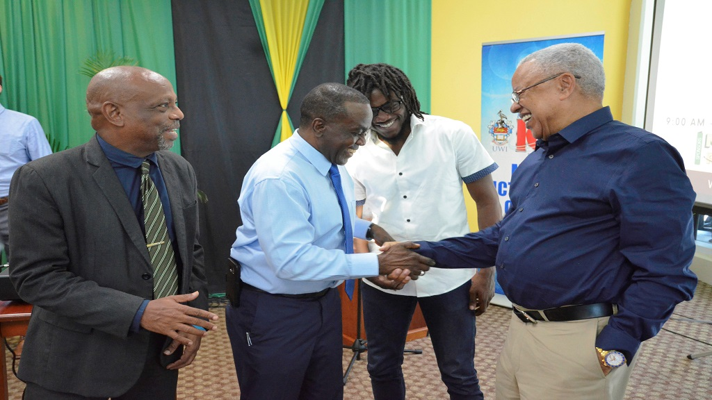 (Left-right) Clyde Mckenzie, Director of FIWI Choice, Christopher Gayle, Software Developer of Gizzada and Professor Hopeton Dunn, Director of Mona ICT Policy Centre, CARIMAC, greet Douglas Halsall Chairman of Advanced Integrated Systems at the CARIMAC National CyberSecurity Conference at the UWI Regional  Headquarters recently.