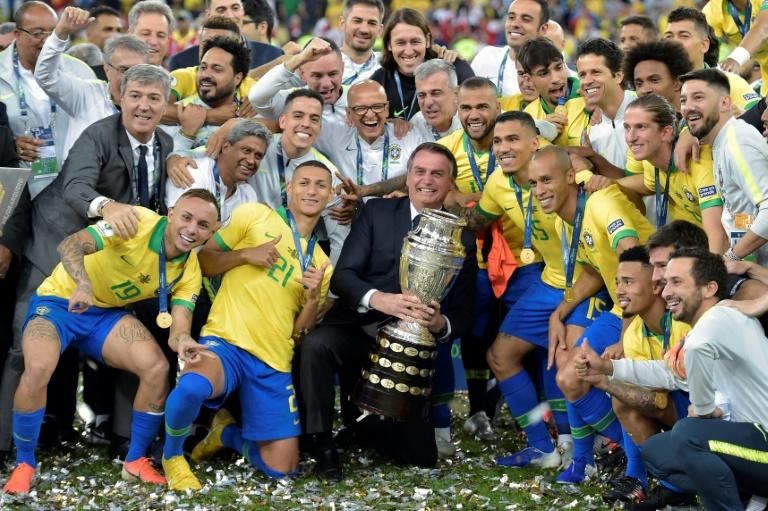 Le président du Brésil Jair Bolsonaro (c) pose avec les joueurs et le trophée après la victoire face au Pérou en finale de la Copa América, le 7 juillet 2019 à Rio de Janeiro