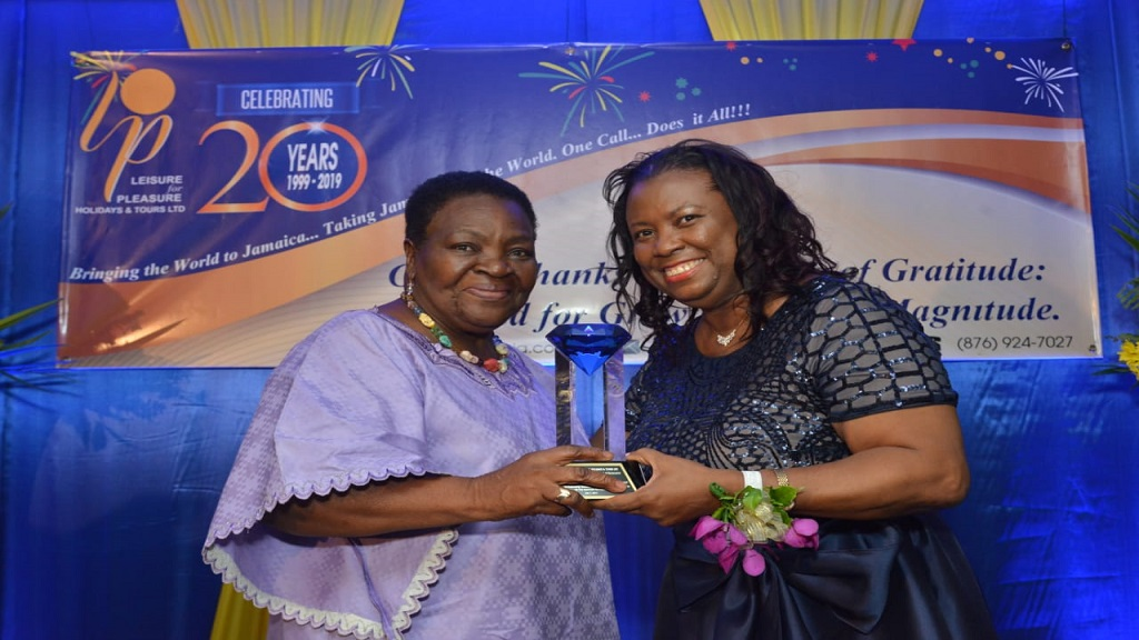Managing Director, Judith James-Watts is all smiles as she presents top client award to  Jasemine Pottinger at the recently held Leisure For Pleasure Holidays and Tours Ltd's 20th Anniversary Awards Luncheon.