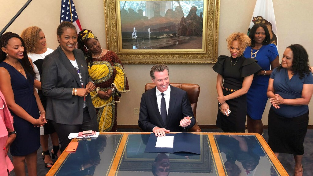 California Gov. Gavin Newsom, middle, signs State Bill, SB-188 Discrimination: hairstyles by state Sen. Holly Mitchell of Los Angeles, third from left, that bans workplace and school discrimination against black people for wearing natural hairstyles, including locks and braids. (AP Photo/Kathleen Ronayne)