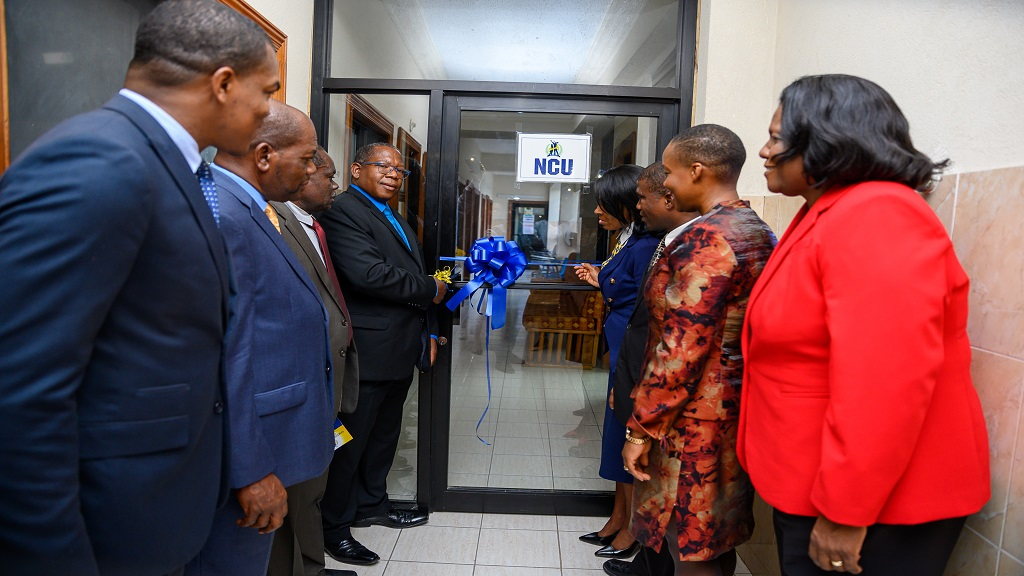 Dr Lincoln Edwards (fourth left), President of the Northern Caribbean University, cuts the ribbon to mark the official opening of NCU's North Jamaica Regional Campus in St Ann's Bay, St Ann, on Thursday, June 28. Looking on are members of the university's senior faculty and members of the St Ann business community.