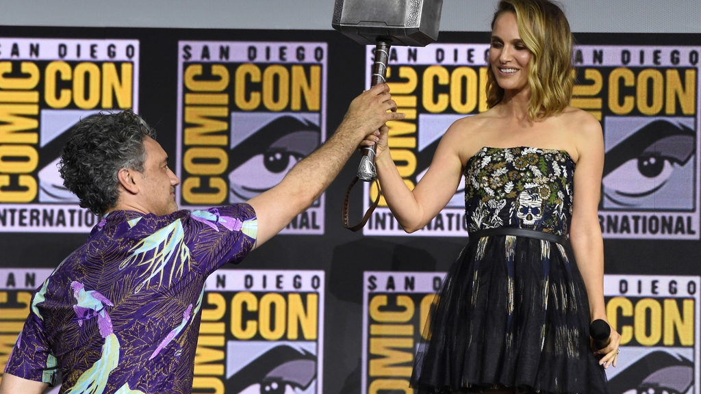 "Director Taika Waititi hands the Thor hammer to Natalie Portman during the ""Thor Love And Thunder"" portion of the Marvel Studios panel on day three of Comic-Con International on Saturday, July 20, 2019, in San Diego. (Photo by Chris Pizzello/Invision/AP)"