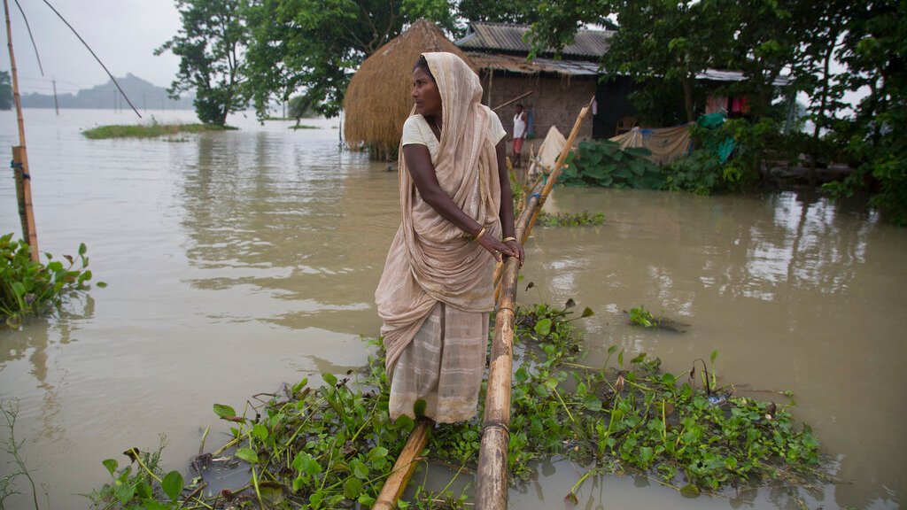 An Indian woman crosses flood waters in Mayong village east of Gauhati, India, Sunday, July 14, 2019. Officials in northeastern India said more than a dozen people were killed and over a million affected by flooding. Rain-triggered floods, mudslides and lightning have left a trail of destruction in other parts of South Asia. (AP Photo/Anupam Nath)