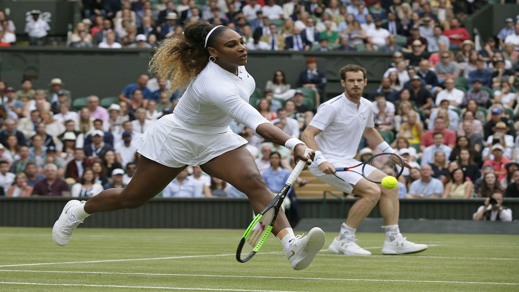 United States' Serena Williams, left, is watched by playing partner Andy Murray as she plays a shot during a mixed doubles match on day six of the Wimbledon Tennis Championships in London, Saturday, July 6, 2019. (AP Photo/Tim Ireland).