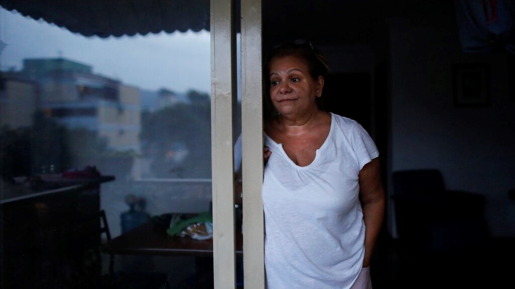 Orelis Lehmann stands on the balcony 's door of her dark apartment in Caracas, Venezuela, Tuesday, July 23, 2019. A power outage that began Monday afternoon at the start of rush hour was one more in a series of prolonged blackouts that have unnerved Venezuelans this year and also hit hard the building where Lehmann lives. (AP Photo/Ariana Cubillos)