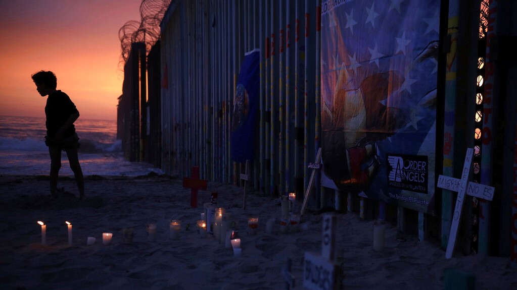 A youth stands by the border fence that separates Mexico from the United States, where candles and crosses stand in memory of migrants who have died during their journey toward the U.S., in Tijuana, Mexico, late Saturday, June 29, 2019. (AP Photo/Emilio Espejel)