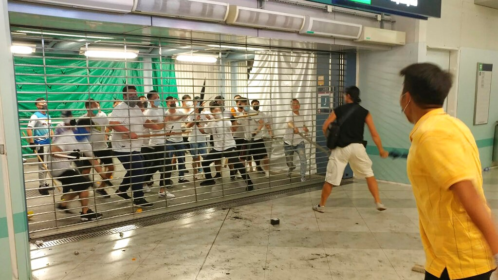 In this Sunday, July 21, 2019, photo, men in white shirts armed with metal rods and wooden poles attack commuters at a subway station in New Territory in Hong Kong. Hong Kong is reeling after a large gang of men in white shirts brutally beat dozens of people inside a train station in a shocking new twist to the city's summer of protest. (Apple Daily via AP)