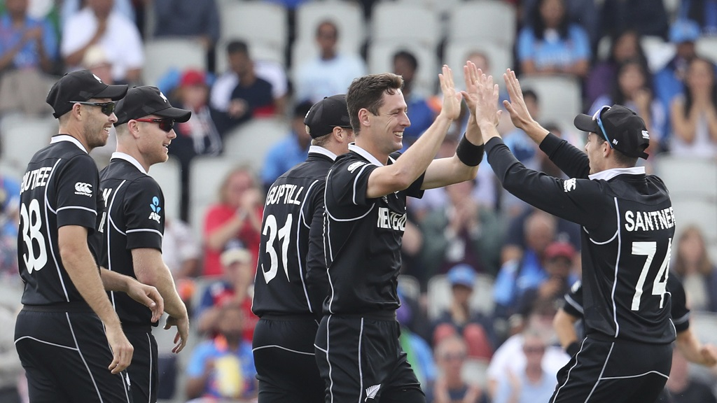 New Zealand's Matt Henry, without cap, celebrates with teammates after dismissing India's Rohit Sharma during the Cricket World Cup semifinal match at Old Trafford in Manchester, Wednesday, July 10, 2019. (AP Photo/Rui Vieira).
