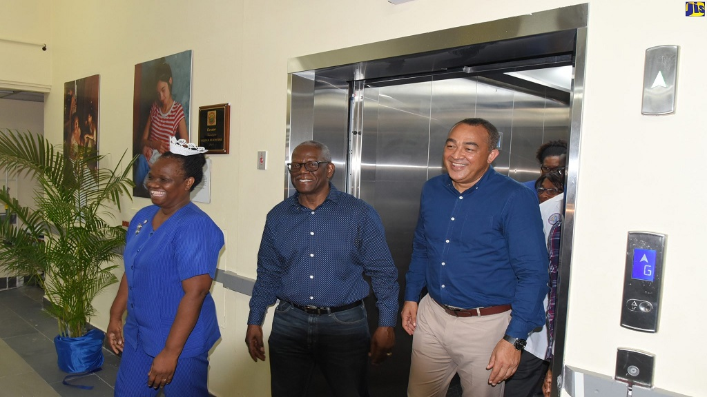 Health and Wellness Minister, Dr Christopher Tufton (right), disembarks the newly installed elevator at the Victoria Jubilee Hospital in downtown Kingston following a ceremony there on Friday. Tufton is accompanied by Director of Nursing Services, VJH, Elsie Fairweather-Blackwood, and Chairman, South East Regional Health Authority (SERHA), Wentworth Charles.