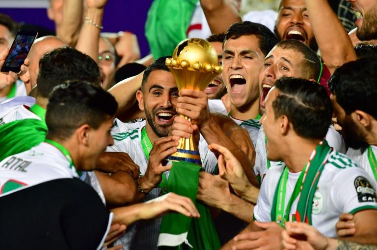L'attaquant Riyad Mahrez (c) soulève le trophée après la victoire de l'équipe d'Algérie contre le Sénégal en finale de la CAN-2019, le 19 juillet 2019 au Caire