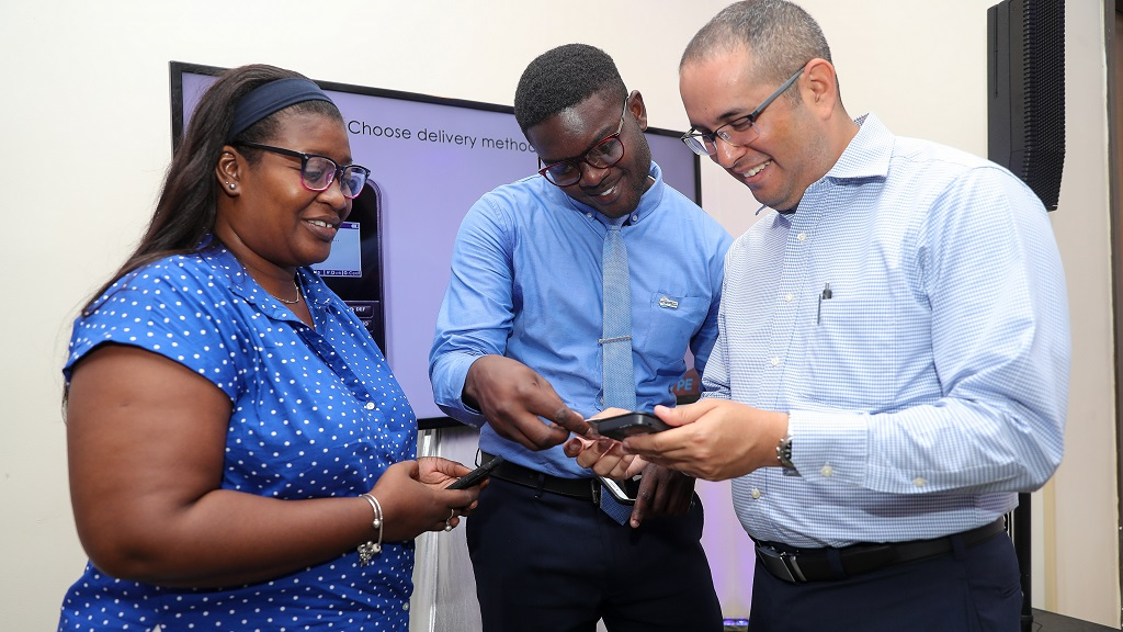 Kevin Chin Shue (right), Assistant Vice President, Payments, Sagicor Bank, demonstrates the use of the Sagicor SWYPE machine to (from left) Betty-Ann Palmer, Nail Technician, La Chateau Nail Design; and Javonie Graham, Accounting Clerk, Insurance Company of the West Indies, during a merchant training session by Sagicor Bank at the Courtyard by Marriott on June 25.