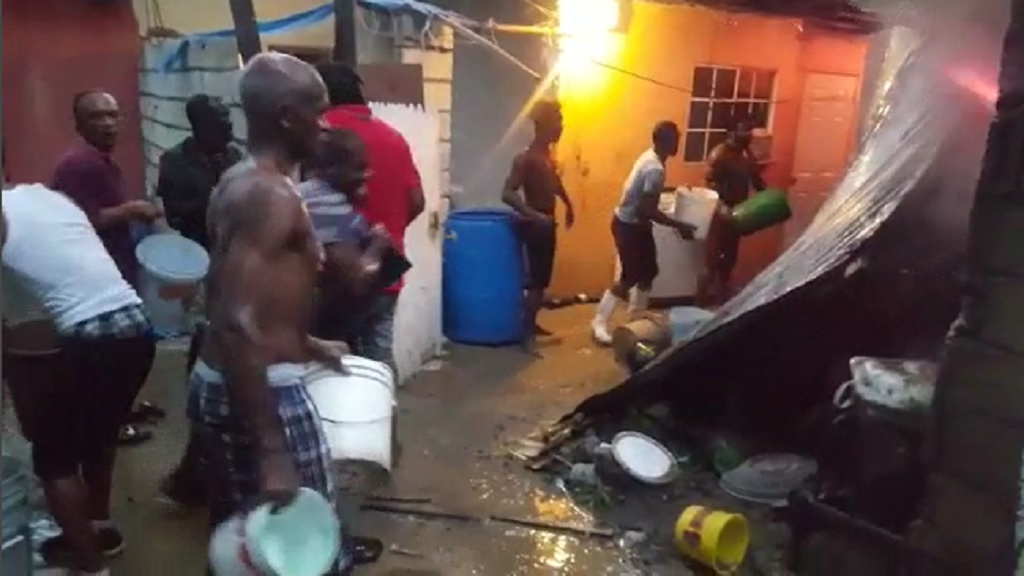 Residents attempt to extinguish a fire in Grants Pen, St Andrew on Monday evening.