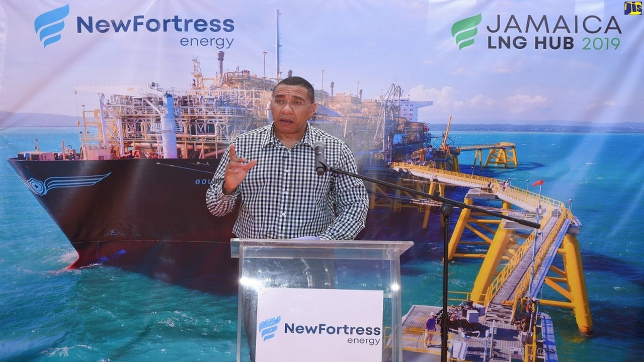 Prime Minister Andrew Holness addresses attendees at a ceremony on Friday to officially commission into service New Fortress Energy's Floating Storage and Regasification Terminal off the coast of Old Harbour Bay in St Catherine, a picture of which is shown on the banner in the background. (Photos: JIS and Reginald Allen)