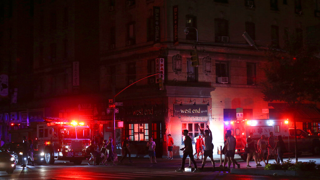 Pedestrians cross the street near emergency response vehicles at 50th Street and 8th Avenue during a power outage, Saturday, July 13, 2019, in New York. (AP Photo/Michael Owens)