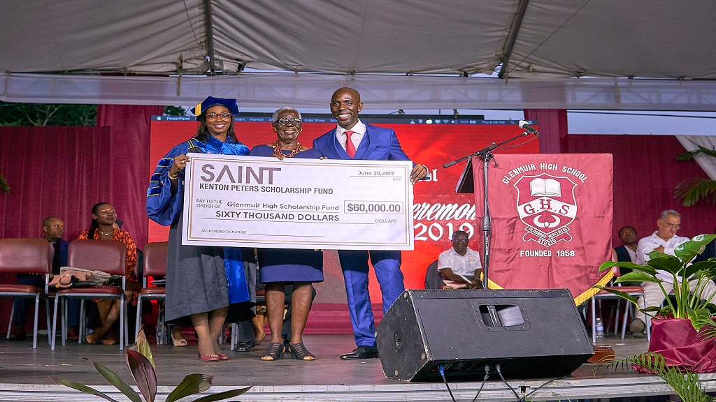 Saint International CEO Deiwght Peters presenting the symbolic cheque to his alma mater, Glenmuir High at the school's recent graduation ceremony.