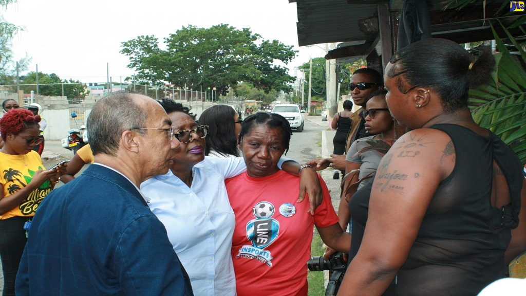 National Security Minister, Dr Horace Chang (left), and Member of Parliament (MP) for South West St Andrew, Dr Angela Brown Burke (second left), interact with residents of Majesty Gardens in St Andrew during a tour of the area by Chang last Friday.