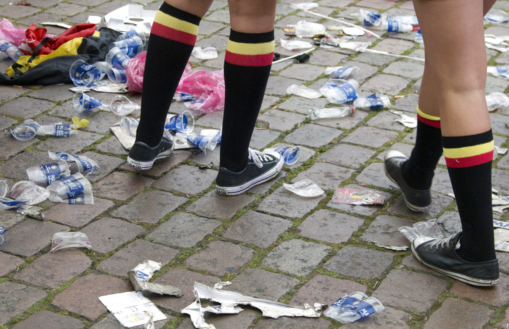 In this June 18, 2016 file photo two Belgian fans, wearing the Belgian colors, walk through plastic cups and other garbage after taking part in a celebration in Antwerp, Belgium, after Belgium won its Euro 2016 Group E match against Ireland. European Union officials have agreed to ban some single-use plastics, such as disposable cutlery, plates and straws, in an effort to cut marine pollution. (AP Photo/Virginia Mayo, file)