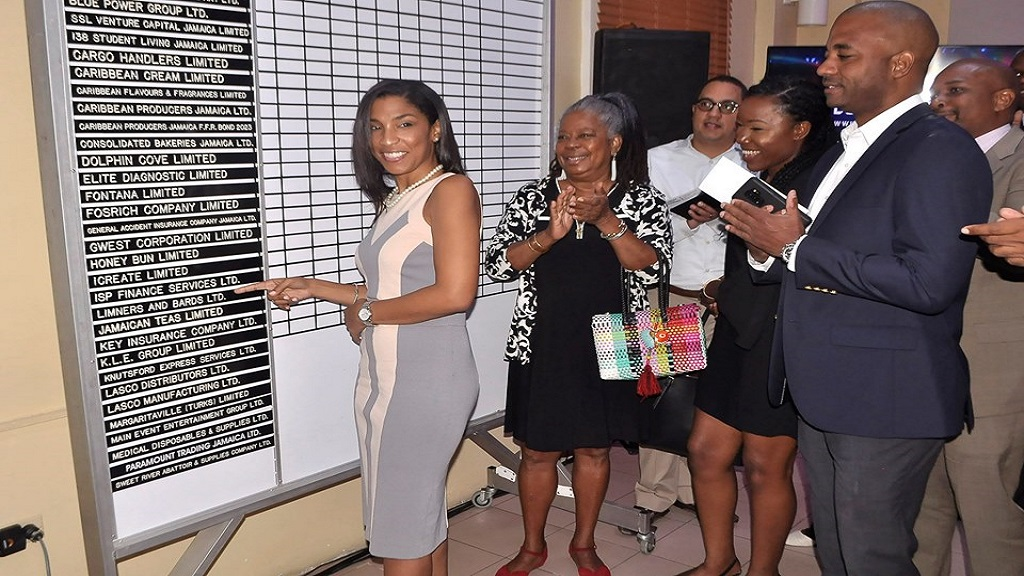 Kimala Bennett, CEO of The LAB places the company's sticker on the JSE trading board during its recent listing ceremony. Photo via JSE, Facebook.