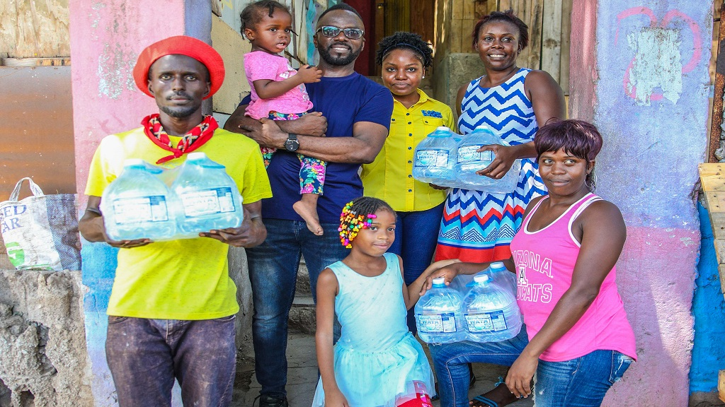 Comedian Ity Ellis (c) and (front row L-R:) Ricardo Foster, his niece Chris Ann, sister Laphane Bent; (back row L -R) nieces Isabel (in hand) and Kenisha Morris and daughter Najali outside their family home on 3rd Street in Trench Town. Ity partnered with Wata to distribute free product to other families in the community.