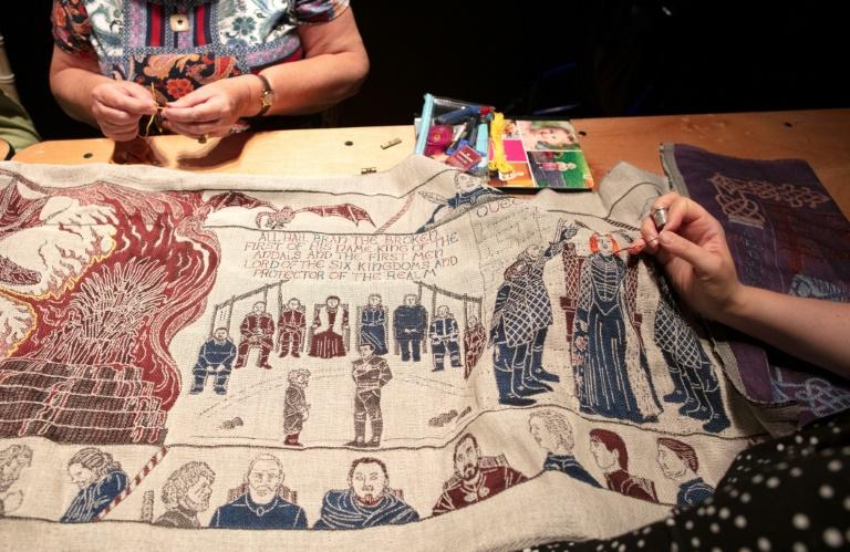 """Dans un musée de Belfast, des brodeuses apportent la touche finale à une immense tapisserie conçue pour rendre hommage à la série """"Game of Thrones"""", le 5 juillet 2019 en Irlande du Nord"""
