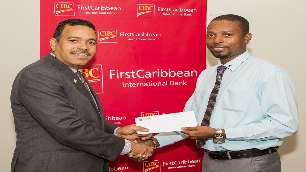 Nigel Holness (left), Managing Director, CIBC FirstCaribbean International Bank presents Duane Cargill, First Vice President of the Kiwanis Club of North St. Andrew, with a sponsorship cheque towards the Club's annual golf tournament.