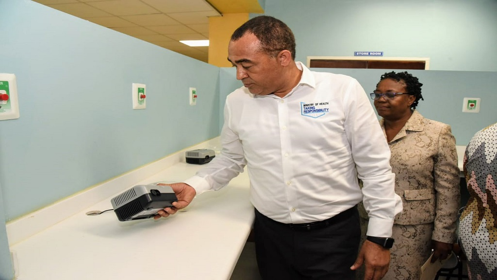 Minister of Health and Wellness, Dr Christopher Tufton (left), looks at a piece of equipment in the renovated Accident and Emergency (A&E) Department at the Princess Margaret Hospital in St Thomas at the official reopening on Thursday. Acting Parish Manager, St. Thomas Health Services, Pauline Bryan-Ellington, observes.
