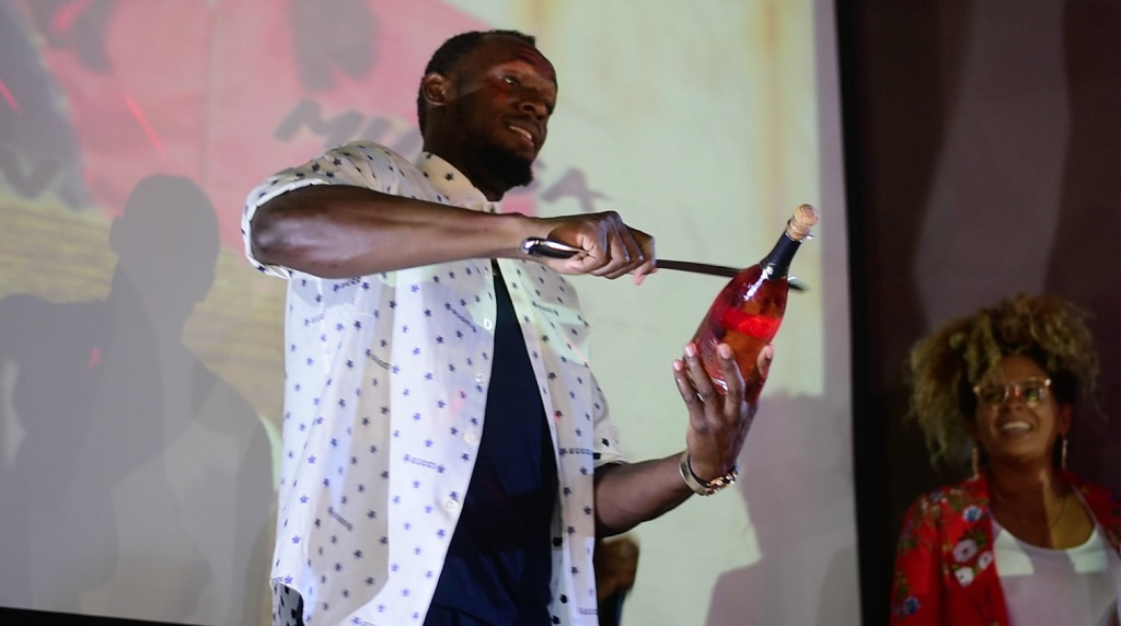 Usain Bolt pops a bottle of his Olympe Rose champagne at the launch event on Thursday.
