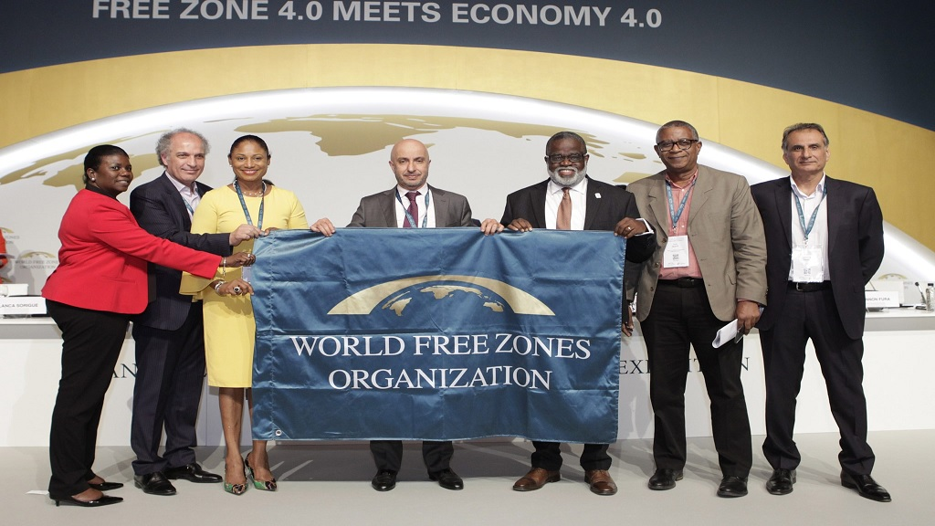 CEO of Jamaica Special Economic Zones Authority (JSEZA), Dr Eric Deans (third right), joins in displaying the WFZO banner at the organisation's 2019 conference held in Barcelona, Spain, in June. From left are Senior Director, Technical Services and Infrastructure Development, JSEZA, Sanvia Martin-Bailey; CEO, WFZO, Dr Samir Hamrouni; Regional Director, Jamaica Tourist Board, Odette Soberam Dyer; Chairperson, WFZO, Dr Mohammed Alzarooni; COO, JSEZA, Gary Scott; and Director, Operations, WFZO, Suresh Poduval.