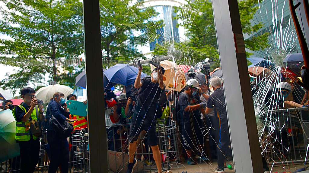 A protester tries to break the glass to get into the Legislative Council in Hong Kong Monday, July 1, 2019. Combative protesters are staging a protest outside the Hong Kong legislature as a crowd of thousands prepares to start a march in that direction. (Jeff Cheng/HK01 via AP)