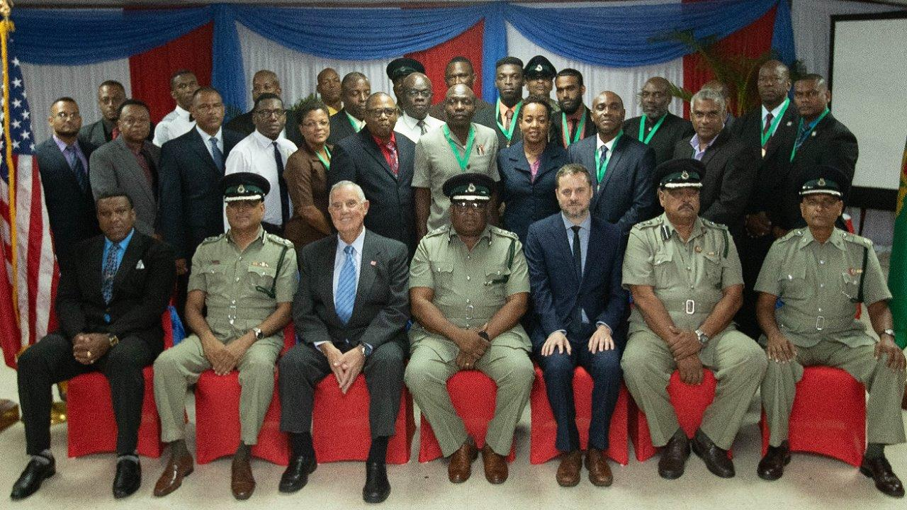 Front row Ambassador Joseph Mondello (third from left), Acting Prisons Commissioner Dane Clarke (fourth from left), and Embassy Political Officer Jason Hammontree (fifth from left), together with senior Prison Service officers and some of the graduates.