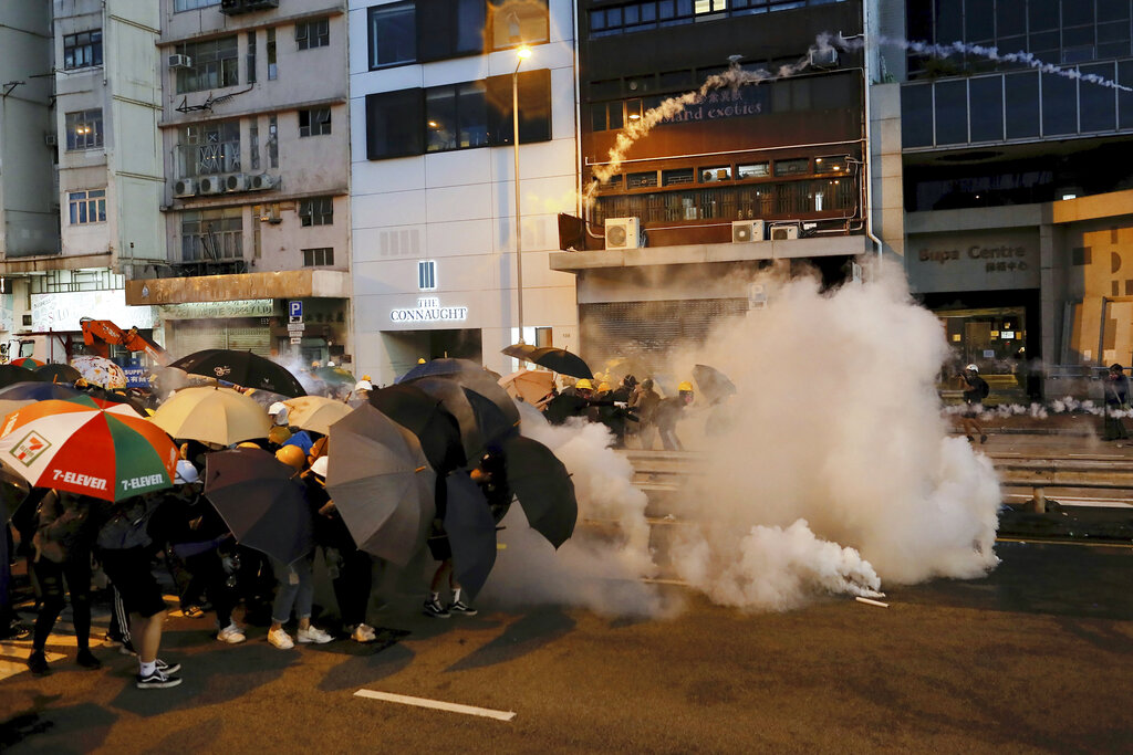 Protesters use umbrellas to shield themselves from tear gas fired by policemen as they face off on a streets in Hong Kong, Sunday, July 28, 2019. (AP Photo/Vincent Yu)