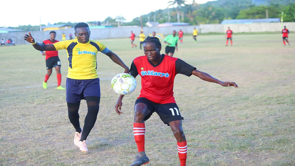 Axum SC's Cecil Bell (right) attempts to control the ball ahead of Grays Inn's captain Howard Malcolm  during the 2019 JP St Mary's/St Mary Football Association Major League Finals on Sunday July 14, 2019 at Westmoreland Oval.