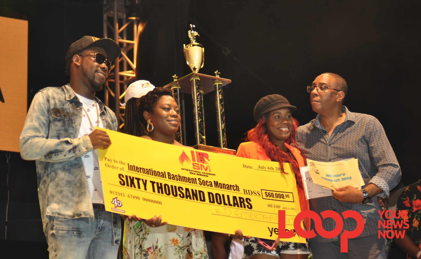 In winner's circle: International Bsshment Soca Monarchm SK (left) along with Stephanie Chase (second right), a representative for King Bubba FM, who also tied in first position, accepts the $60,000 prize check, trophy and other prizes from Minister of Culture, the Creative Economy and Sports, John King.