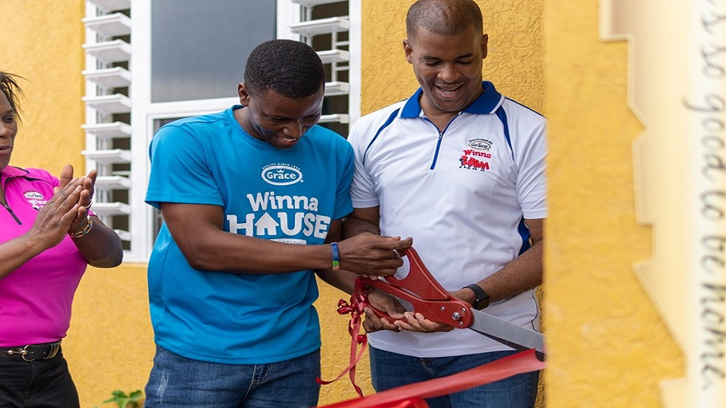 Frank James (right) CEO of GraceKennedy's Domestic Foods Division gives Romario Grant, the Grace Foods Winna House winner a hand to cut the ribbon during the promotion's grand finale.