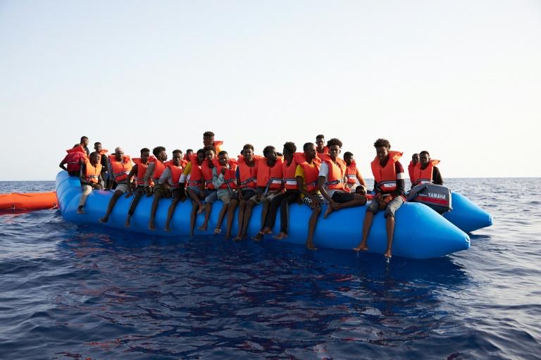 Photo prise et difffusée le 5 juillet 2019 par l'ONG allemande Sea-Eye montrant des migrants à bord d'un canot pneumatique surchargé repéré dans les eaux internationales au large de la Libye