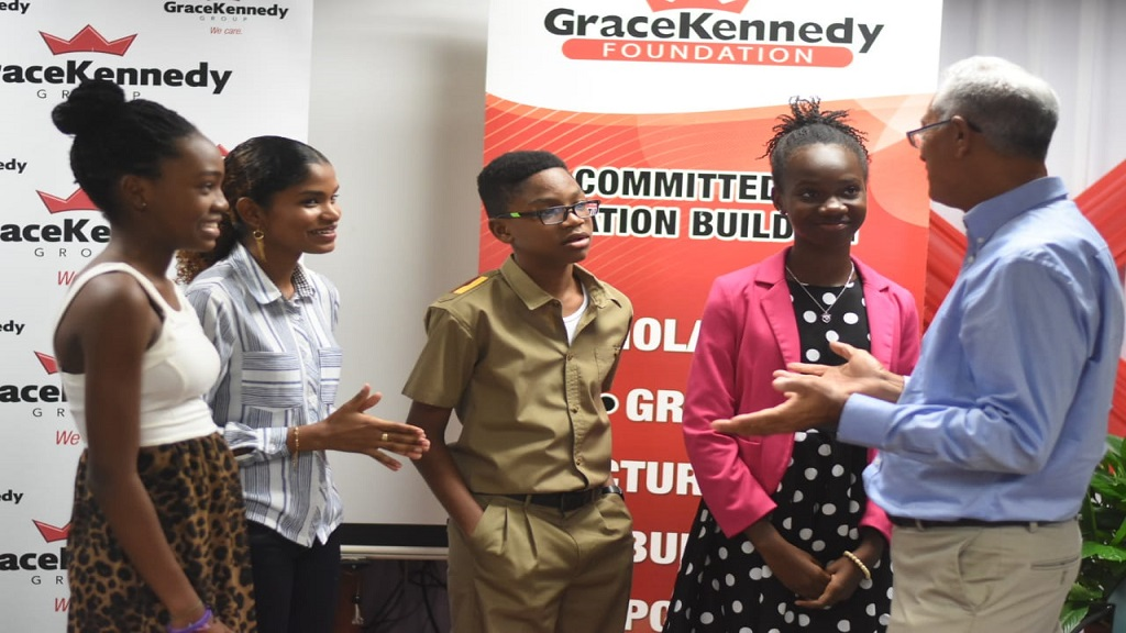Carlton Alexander Memorial bursary award recipients listen attentively to a GraceKennedy executive after the ceremony.