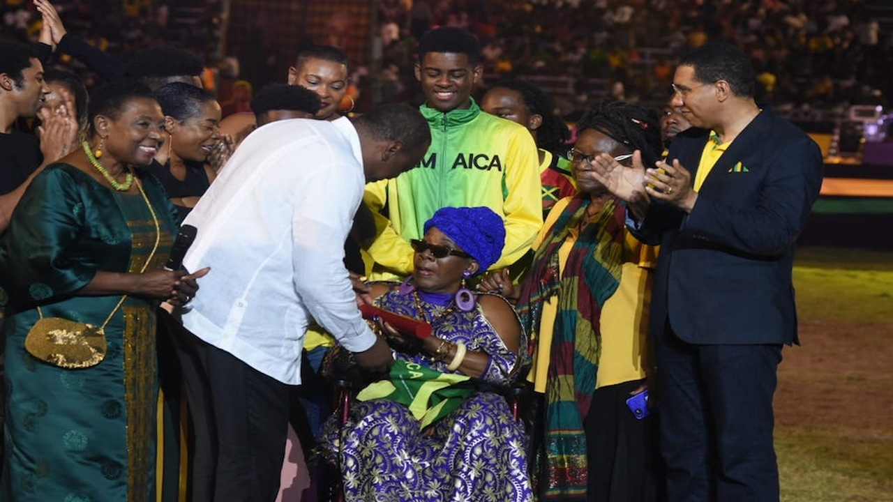 Rita Marley (centre) collects her citation from Kenya president Uhuru Kenyatta (second left) at the Independence Grad Gala on Tuesday. Prime Minister Andrew Holness (right), Culture Minister Olivia Grange (left) and Marley's relatives share in the occasion. (PHOTOS: Marlon Reid)