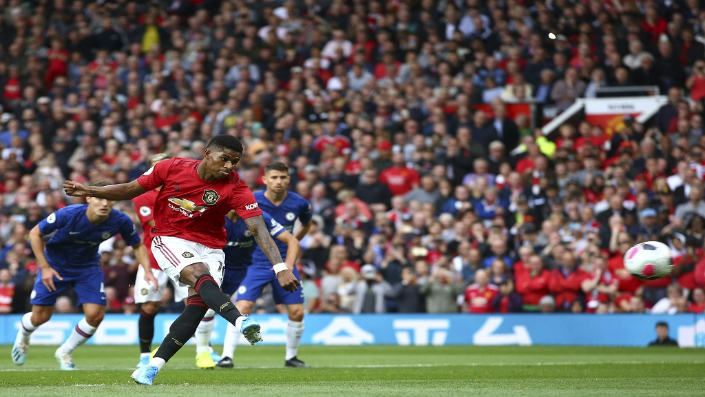 Manchester United's Marcus Rashford shoots a penalty kick to score his sides first goal during the English Premier League match between Manchester United and Chelsea at Old Trafford in Manchester, England, Sunday, Aug. 11, 2019. (AP Photo/Dave Thompson)