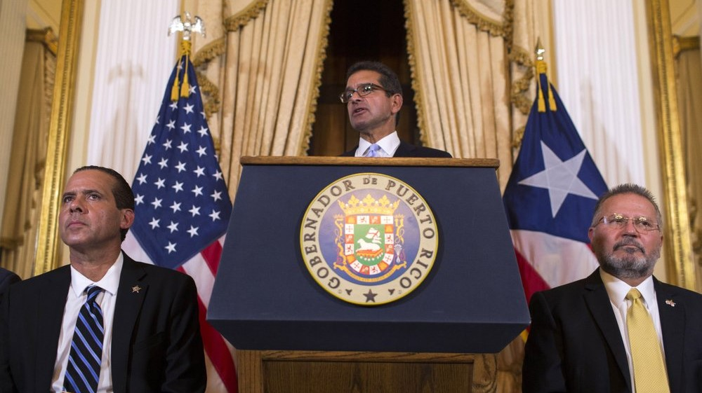 Pedro Pierluisi, sworn in as Puerto Rico's governor, speaks during a press conference, in San Juan, Puerto Rico, Friday, Aug. 2, 2019. Departing Puerto Rico Gov. Ricardo Rossello resigned as promised on Friday and swore in Pierluisi, a veteran politician as his replacement, a move certain to throw the U.S. territory into a period of political chaos that will be fought out in court. Pierluisi is flanked by lawmakers Jorge Navarro, left and Jose Aponte. (AP Photo/Dennis M. Rivera Pichardo)