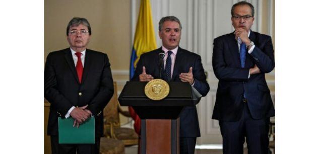 Le président colombien Ivan Duque (c), le ministre des Affaires étrangères Carlos Holmes Trujillo (g) et le procureur général Fernando Carrillo, lors de la signature d'un décret permettant la naturalisation de 24.000 enfants de parents vénézuéliens nés sur le sol colombien, le 5 août 2019 à Bogota ((c) Afp)