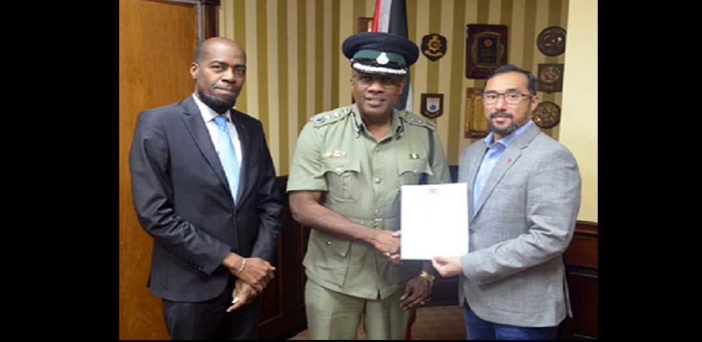 Minister of National Security the Honourable Stuart R. Young M.P. (right) presents Mr. Gerard Wilson (centre) with his Instrument of Appointment as Commissioner of Prisons. Also present to congratulate Commissioner Wilson is Permanent Secretary of the Ministry of National Security Mr. Vel Lewis (left).