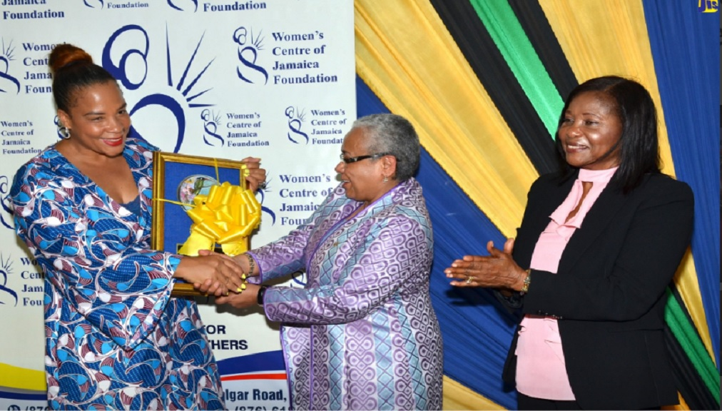 Wife of the President of the Republic of Kenya, Margaret Kenyatta (centre) is presented with a gift by Chairman, Women's Centre of Jamaica Foundation (WCJF), Debby Ann Salmon (left), during a visit to the WCJF in St. Andrew on Monday. Looking on is wife of the Governor-General, Lady Allen.