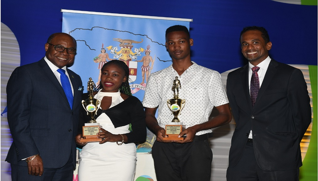 Minister of Tourism, Edmund Bartlett (left) poses with the exceptional performers (male and female) in the Tourism Enhancement Fund's (TEF) Summer Internship Programme (SIP) Le-Ann Connell (2nd left) and Shemar Findley (2nd right).  The occasion was the SIP closing ceremony, which took place today at the Courtleigh Auditorium in New Kingston. Enjoying the moment is Dr. Carey Wallace, TEF Executive Director.