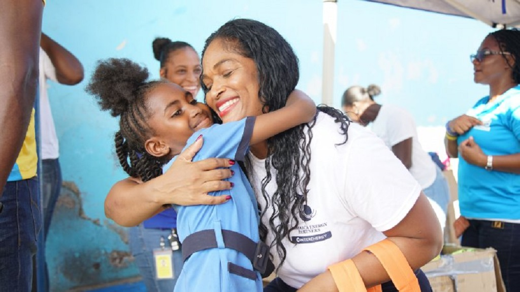 A West Kingston Power Partners staff member embraces a young girl at previously held back-to-school-treat.
