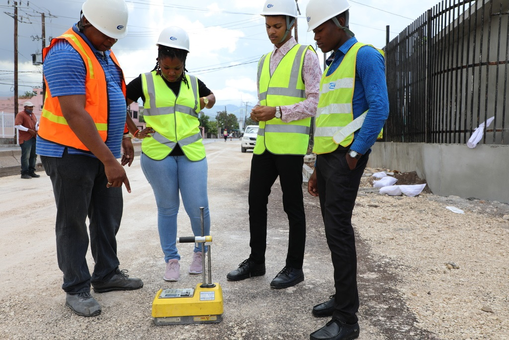 CHEC's Quality Control Engineer Damian Anderson (left) explains the use of a Nuclear Reactor Density Gauge to interns Roxanne Blair, Donrich Dennis and Shamari Hendrickson as they observe roadwork along Hagley Park Road in Kingston.